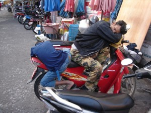Father and son sleep on bike in Chiang Mai